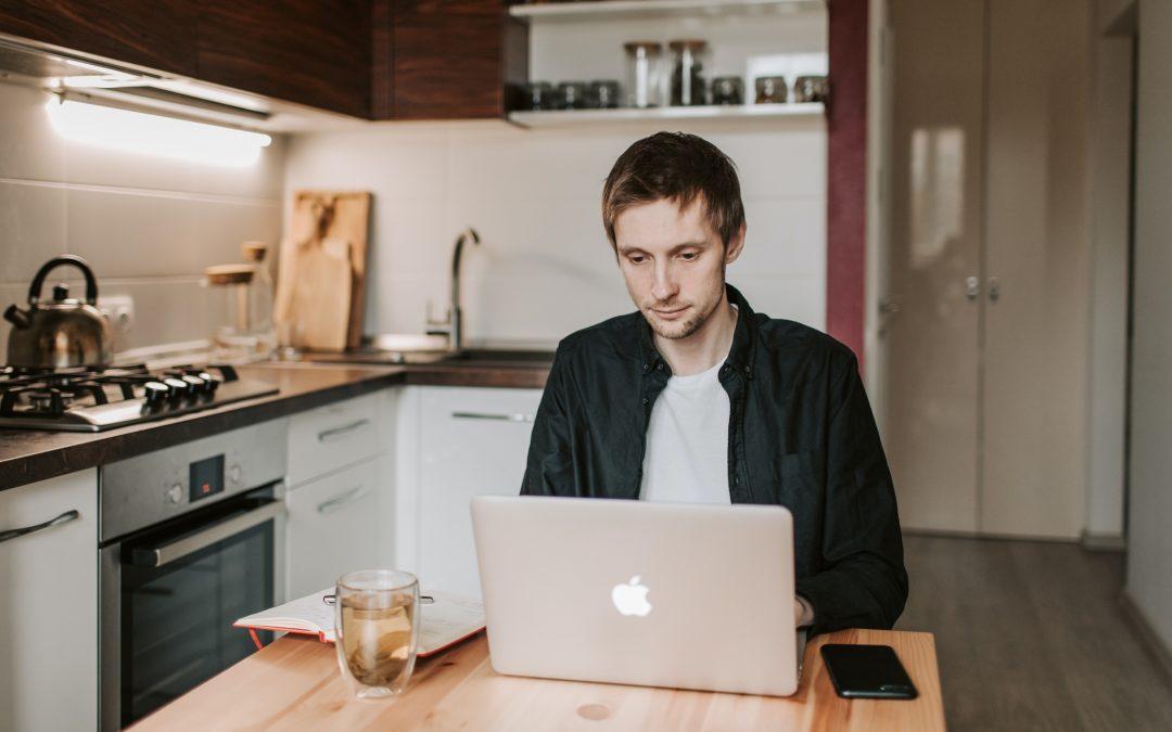 Mann sitzt am Küchentisch am Laptop und arbeitet